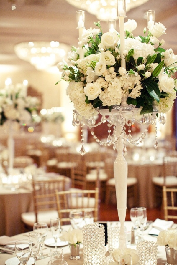 Beautiful white candelabras holding bountiful arrangements of various white flowers & tons of candlelight.