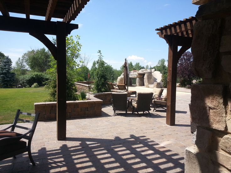 Outside pergola in the backyard with a natural gas fire pit, Swimming pool, diving and jumping faux rock and cave, diving board, Paver sitting walls in Alpine Utah