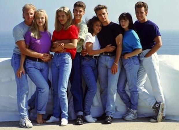 """Every generation has its of-the-moment style of denim. Unfortunately for teens in the 1990s, that style was high-waisted, unnecessarily bunchy in the front, tight in the backend and unflattering in every way. It wasn't until a decade later that Tina Fey, Amy Poehler, Maya Rudolph and Rachel Dratch famously dubbed the style """"Mom Jeans"""" on SNL. But in the 1990s it was the kids who were wearing them—guys and girls—as evidenced in this photo of the entire trend-setting cast of Beverly Hills…"""