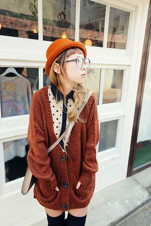 Casual: Dark orange, knitted cardigan. Orange hat. White shirt with black dots and details. Glasses. Black, thigh-high socks. Beige bag.