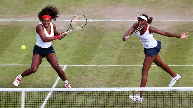 Venus Williams (R) of USA hits a forehand next to her sister Serena during their women's Doubles match against Sorana Cirstea and Simona Halep of Romania on Day 3 of the London 2012 Olympic Games at Wimbledon