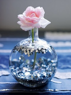 simply spray sequins with a clear glue, funnel them into a vase and shake. They will land primarily in the bottom of the vase, but will stick around elsewhere as well.