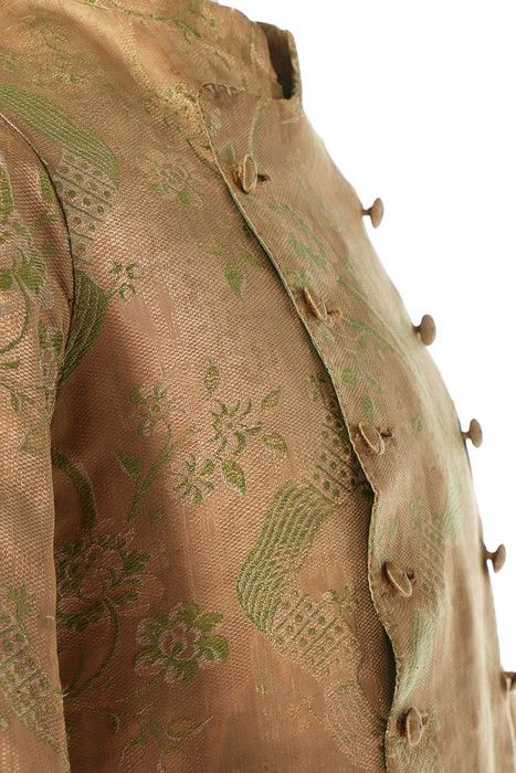 A gentleman's brocaded silk banyan, circa 1760. A gentleman's brocaded silk banyan, circa 1760. of pale peach silk brocaded with ivory and pale green ribbon garlands and blossom, double-breasted with silk cord covered buttons, wide curved sleeves with broad cuffs, short stand collar, pocket slits and two internal linen patch pockets, lined in green taffeta, chest 102cm, 40in