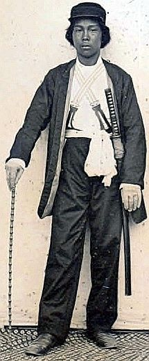 Samurai wearing Western style clothing including suspenders and shoulder carry sword belt, he is holding a muchi (whip), Boshin war era, ca. 1867-1869.