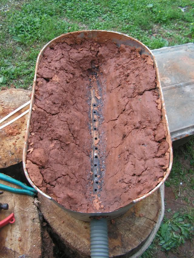 Home forge lined with clay and with a tuyere made out of a steel pipe with multiple holes drilled in it.