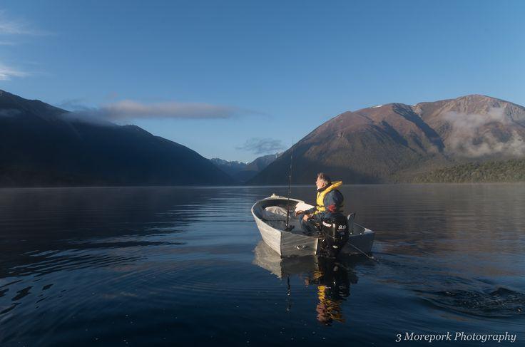 Fisherman heading out early morning on Lake Rotoiti, St Arnaud, South Island.