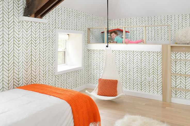 Green and orange toddler bedroom features walls clad in Serena & Lily Feathers Wallpaper lined a wood ladder leading up to a play loft with wood banister alongside a white wicker hanging chair adorned with an orange pillow suspended from the ceiling.