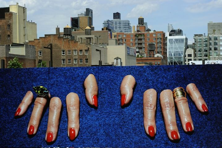 A billboard created by Maurizio Cattelan and Pierpaolo Ferrari hangs in the Chelsea neighborhood of New York on Sunday. The image was created for Toilet Paper, a two-year-old art magazine founded by the two artists, and is part of a High Line Series, which will be on view through June 30. Photo by Timothy A. Clark/AFP/Getty Images.