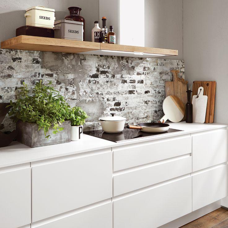 Eine Nischenrückwand im Backstein Dekor und passende Deko verwandelt eine schlichte weiße Küchenzeile in eine trendige Industrial Style Küche