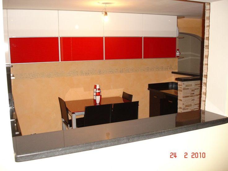 Masa bucatarie realizata din sticla vopsita rosu dotata cu sisteme de lifting Aventos HF de la Blum