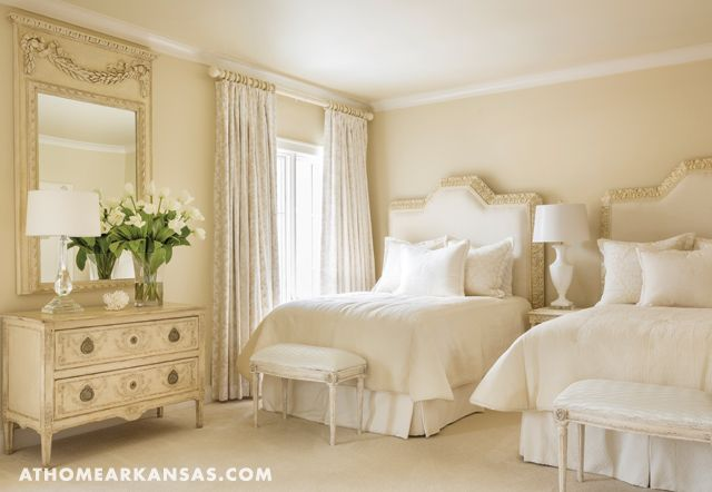 "A guest bedroom with twin beds is Davis's ""favorite room in the home."" An antique chest coordinates with delicate Amy Howard benches and custom headboards and bedding."