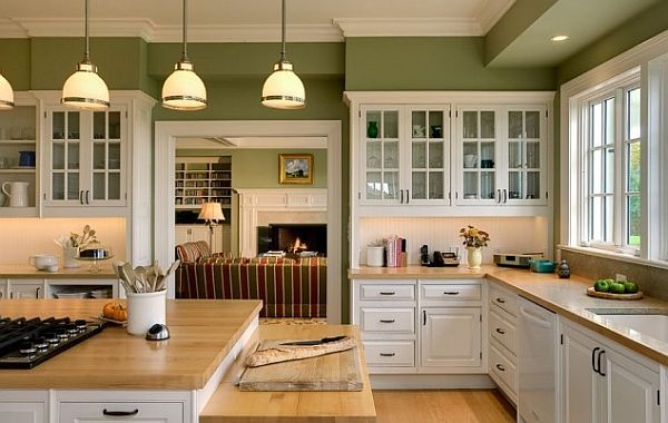 Fresh kitchen colors. White kitchen cabinetry with wooden furnishings and green walls