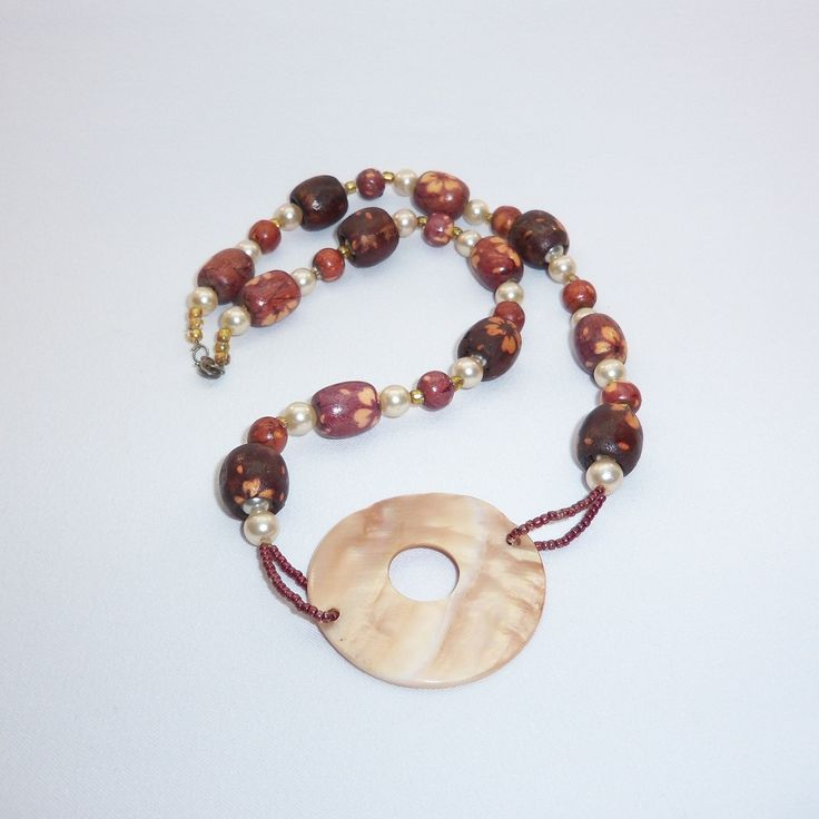 Ожерелье Символ выполнено из деревянных, пластиковых бусин и центрального элемента из перламутра. Длина ожерелья 60 см, размер центрального элемента 5 см.