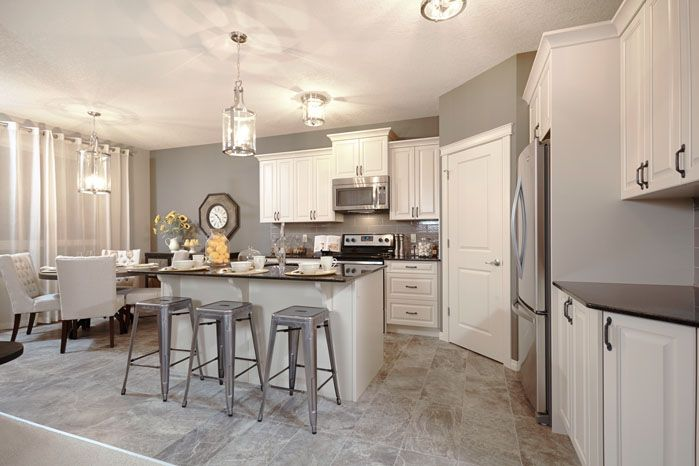 Kitchen with central island and pantry in the Orion II showhome in King's Heights in Airdrie by Shane Homes