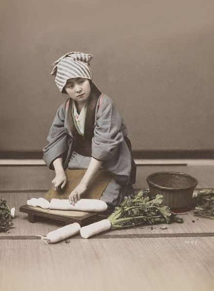 Young woman wearing a grey kimono and blue and white striped head scarf, cutting up daikon radishes.  About 1900, Japan