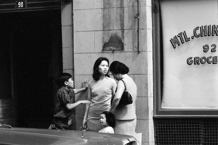 6. «Le quartier chinois» — rue De La Gauchetière Ouest, vers 1968  Ce cliché témoigne de la transformation du quartier chinois, qui, auparavant habité par des hommes solitaires, devient dans les années 1960 un secteur fréquenté par de jeunes familles. De 1895 à 1947, des lois discriminatoires limitaient l'immigration des Asiatiques au Canada — ce qui rendait presque impossible pour un grand nombre d'hommes de faire venir conjointes et enfants à Montréal.