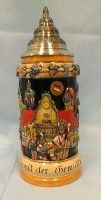 """This Oktoberfest Relief-Stein is crowned by an antiqued pointed solid pewter lid and is decorated with a Brass band on the front.  The handle has the word Oktoberfest on each side of it. There is a text on the base """"Ein Prosit der Gemütlichkeit"""" (Three Cheers to festivity)."""