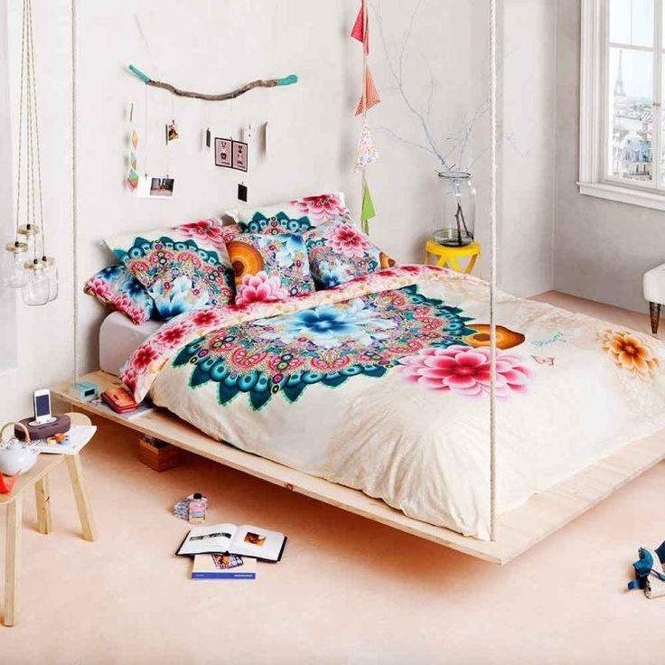 chambre à coucher de style hippie chic avec un lit suspendu et literie à motifs floraux bleus et roses