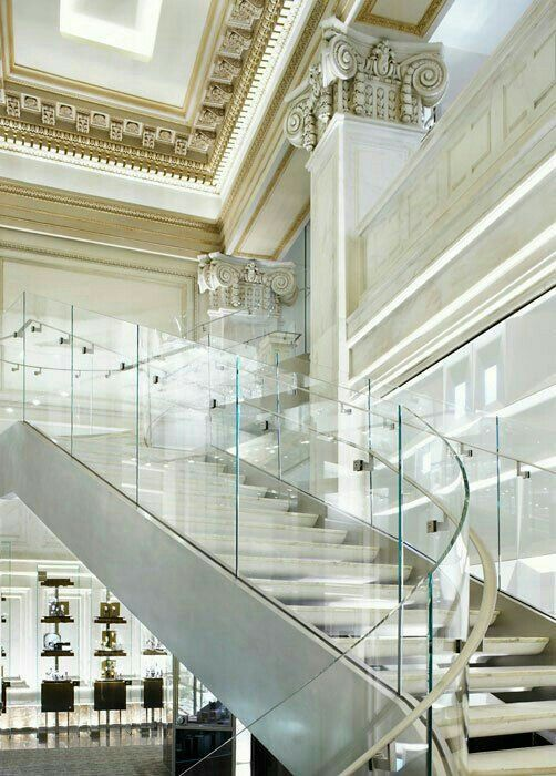 A transparent staircase railing again with white n gold colors on wall and ceiling to add royality to the lobby n staircase