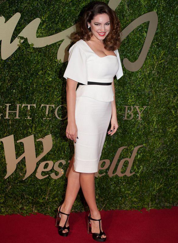 Kelly Brook con un vestido midi de escote cuadro ceñido a la cintura, combinado con sandalias negras de tacón joya.