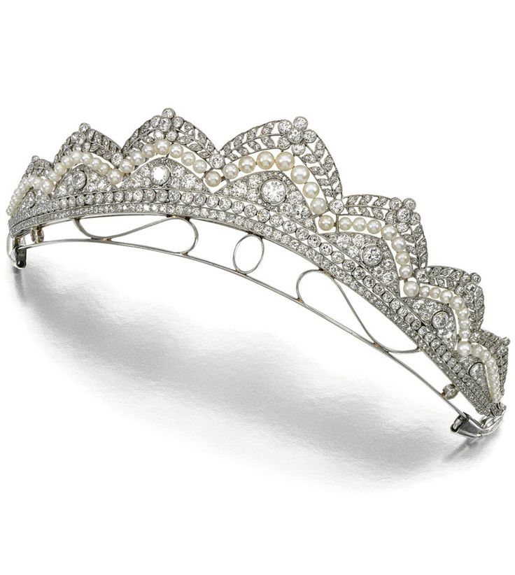 PEARL AND DIAMOND TIARA, CIRCA 1910. In the Garland Style, designed as a series of graduated  open work arches, to a central undulating line of pearls, millegrain-set with circular-, single- and rose-cut diamonds with stylised laurel and flower head motifs to the surmount, inner circumference approximately 180mm, fitted case by J.C. Burnier& Zoon, Juweliers, Den Haag.