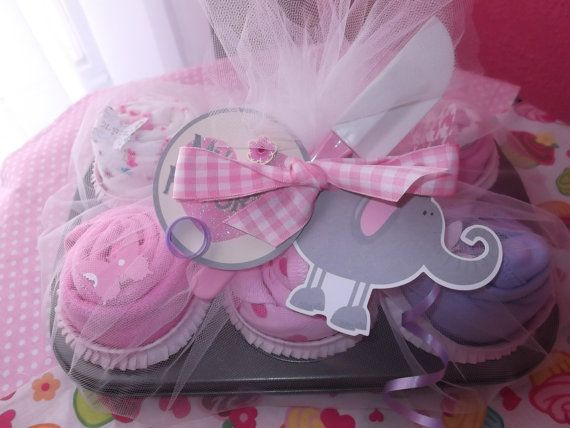 Cupcakes made from onesies, burp cloths, washcloths, pants, bibs, etc. Just roll up, put into a cupcake tin, wrap with tulle, and tie with ribbon. Cute.