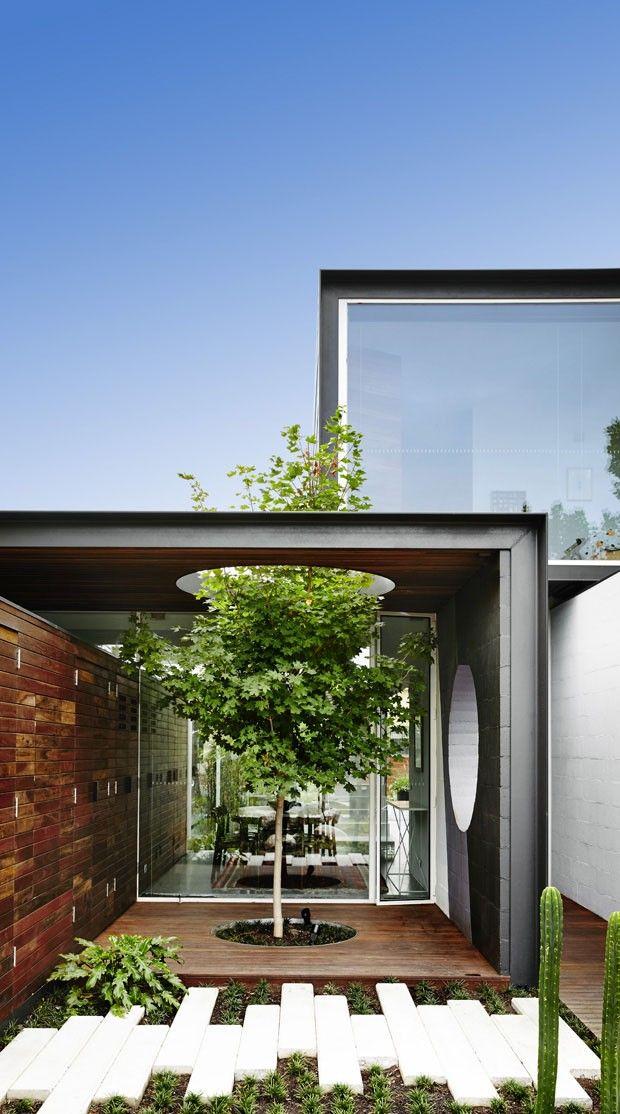 Vidros amplos, jardim contemporâneo e escada vazada se destacam em casa na Austrália