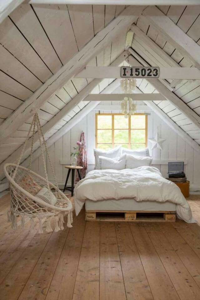 Cozy cottage style bedroom in the attic. Wide plank wood floors. White and wood.