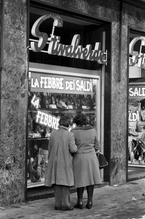 Two women look at the window of a shoe store Stivalverde in the days of sales. Italy, Seventies MONDADORI PORTFOLIO/Adriano Alecchi