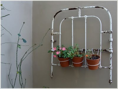 Wall art/planter from an old bedhead...would also look good with a climber trailing through it.