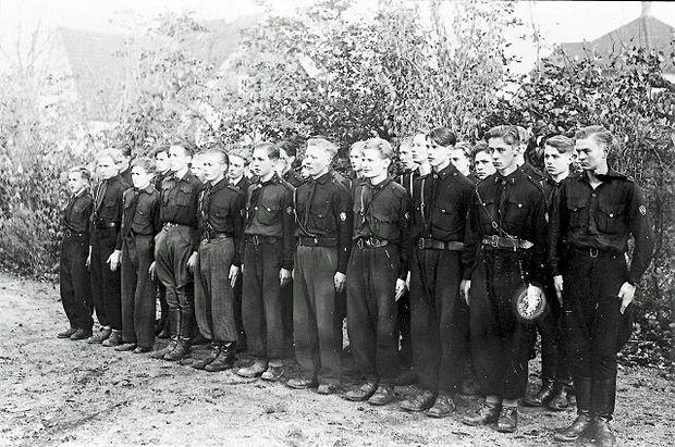 """De sorte spejdere, NSU'erne taget opstilling for at møde en af Schalburgs """"Bloddrenge"""", som skal overbringe hilsener fra NSU-kammeraterne på Østfronten."""