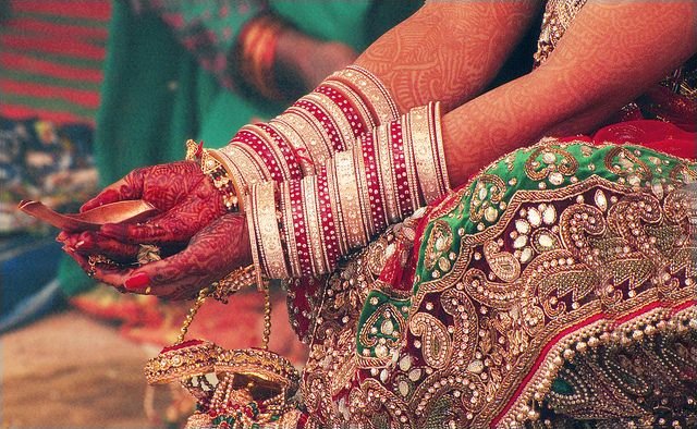 "North Indian Hindu wedding rituals involve the bride wearing dozens of red and cream ivory bangles adorning her wrists. These set of bangles in ivory, lac or plastic with intricate inlay work painted or engraved on it are adorned on the bride's wrist are known as ""Chuda""."