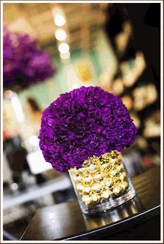 Purple floral centerpiece but i think I want to do red shotgun shells in the bottom instead of Christmas balls