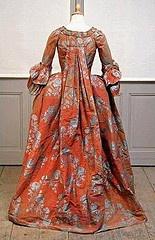 Robe à la française. Vers 1770 (ADJUG'ART)    Damas de soie. Fond rouille et motifs de branches de roses bleu Nattier. Plis dorsaux, corsage fermé par des compères passementés et boutonnés, parements passementés de même tissu, manches pagode à deux volants passeme ntés. Jupe à plis plats de même tissu que la robe. La doublure de la robe est en lin blanc.Conservée dans la même Famille aristocratique bretonne depuis les origines.