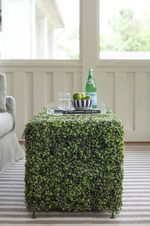 Chic sunroom features a faux grass coffee table atop a gray striped rug.