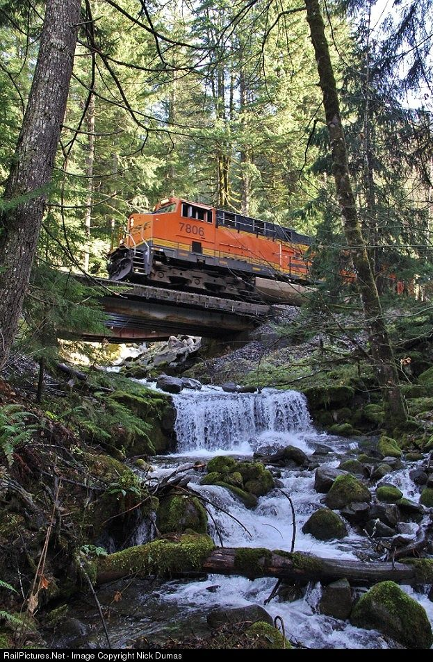 An eastbound BNSF Q train passes over a beautiful waterfall east of Skykomish, WA just after passing over the Foss River Trestle.--Would you climb up underneath this bridge? Would you stay when a train came?
