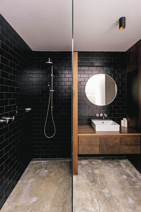 Dark wall tiles in the bathroom are balanced by the softer tones of the concrete floors and timber joinery.