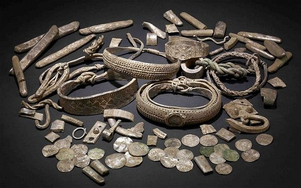 A hoard of 1,000-year-old artefacts including more than 200 coins, ingots & pieces of silver jewellery, found buried in north Lancashire.    The British Museum are examining the hoard after it was discovered in a lead pot by a metal detector enthusiast.     The hoard buried at a time when the Anglo-Saxons were attempting to take control of the north of England from the Vikings.  Contains Anglo-Saxon, Anglo-Viking, German & Islamic coins.    201 silver objects, 27 coins, buried 900AD.