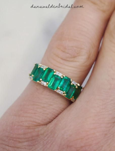 A series of luxurious emerald-cut emeralds are set in staggered sequence and flanked by brilliant white diamonds. Each emerald is slightly different from the next, revealing organic characteristics, and the most mesmerizing shade of green. The glorious warmth of yellow gold creates the perfect backdrop for this artful creation. Wear Allie as a prominent wedding band or as a unique engagement ring. Slip her on independently for a touch of timeless elegance, or pair her with stacks of gold…