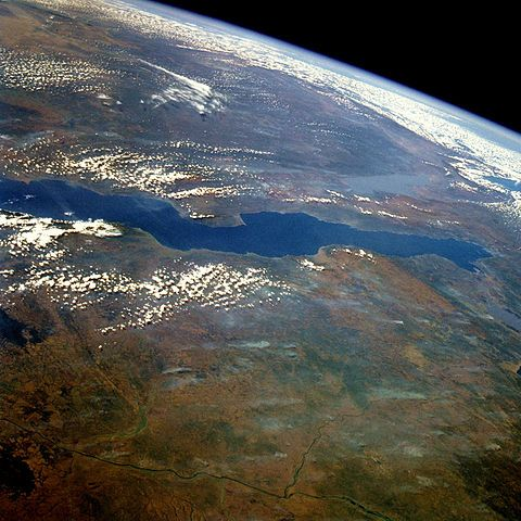Lake Tanganyika is an African Great Lake. It is est. to be the 2nd largest freshwater lake in the world by volume, & the 2nd deepest, in both cases, after Lake Baikal in Siberia. It is the world's longest freshwater lake (420 mi) & accounts for 18% of the world's available fresh water. It is situated w/in the Albertine Rift, the western branch of the East African Rift, & is confined by the mountainous walls of the valley. Wikipedia/ Photo: STS51G-034-0012 Lake Tanganyika June1985