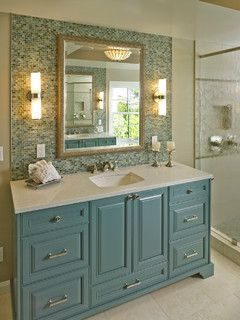 Lovely master bathroom with blue cabinets and glass mosaic tile.
