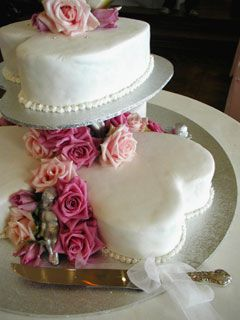 Pictures of Heart Shaped Wedding Cakes -   White heart wedding cake made with four hearts. Beautifully decorated with silver cupids, pink and coral roses and candy pearls around the main focal flower wedding cake topper.