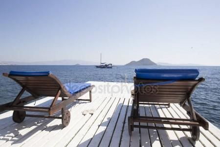 Two white wooden beach chairs on a wooden pier by the sea agains