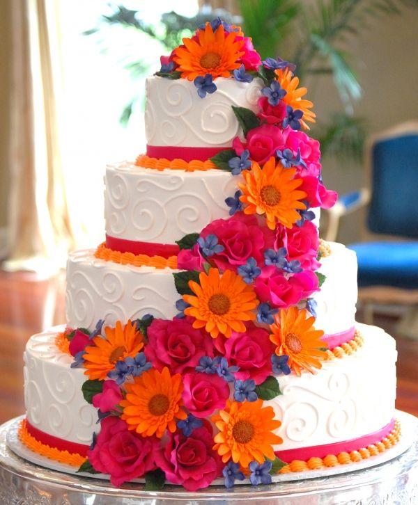 White wedding cake with orange, hot pink, and blue sugar flowers.