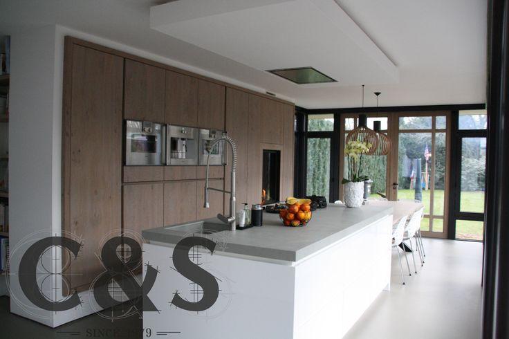 C&S interieurs heeft weer een prachtige keuken opgeleverd. In de apparatenwand is de haard helemaal door ons ingebouwd. Het eiland heeft een keramisch blad met pitt cooking erin verwerkt. De tafel aan het eiland is ook door C&S gemaakt, deze is in de zelfde kleur als de apparaten wand.