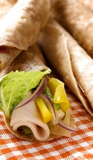 Using half a wrap makes Savory Skinny Wraps easy for small hands. Layer lettuce, cheese, turkey breast and fruit filling, then add chopped bacon if desired. #school #lunch #recipes #sandwich #healthy