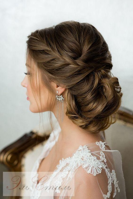 Elegant low bun wedding hairstyle with bold braids, updo hairstyle for vintage or romantic wedding theme.
