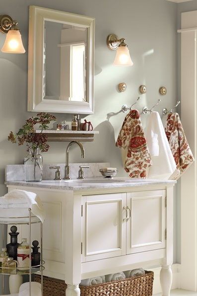 Nice use of space in a small bathroom--Storage under vanity, extra shelf above sink, tiered storage at the side and space saving hooks hang multiple towels.