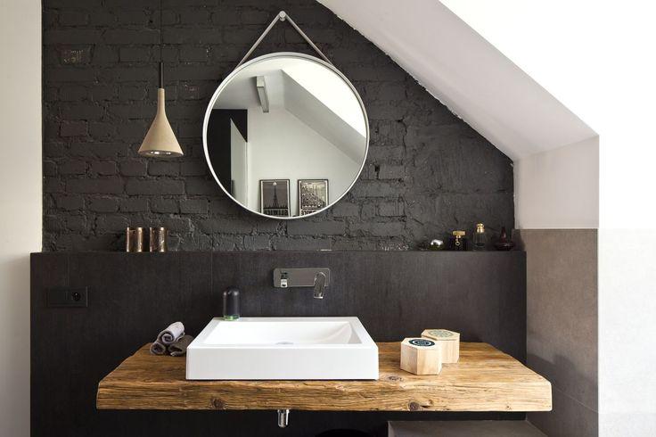 <p>Czarna cegła na ścianie w połączeniu z surowym drewnianym blatem i betonowymi dodatkami zaskakuje harmonią różnorodności w projekcie łazienki na poddaszu. Styl nowoczesny i rustykalny splotły się tu w jedną całość, dając ponadczasowy i formalnie ciekawy projekt łazienki. Zobacz jak w jednym wnętrzu łazienki przeplatają się faktury drewna, cegły i betonu oraz na co zwrócić uwagę wybierając <strong>drewniany blat do łazienki</strong>!</p>