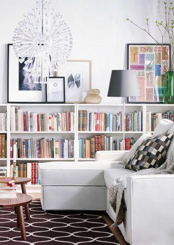 La habitación durante el día. Sofá, sillón, librerías, alfombra, mesas de centro y vitrina de IKEA.